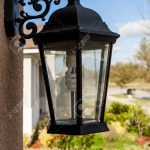 outdoor porch lantern light fixture mounted on house with eco