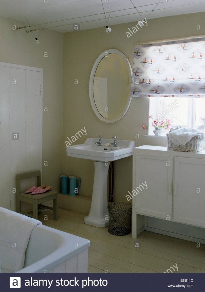 oval mirror above white pedestal basin in country bathroom