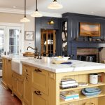 pale yellow kitchen with white cabinets lighting above