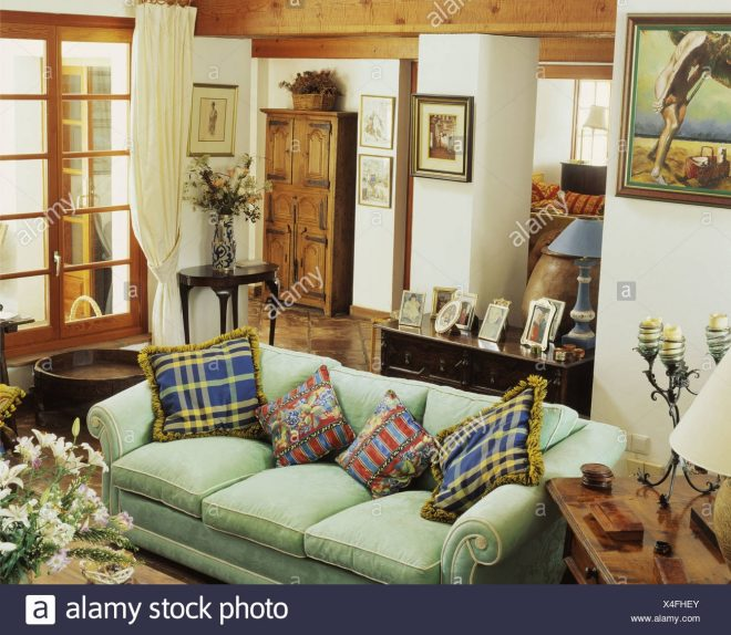 patterned cushions on green sofa in traditional living room