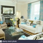 patterned turquoise curtains on window above white sofa in white