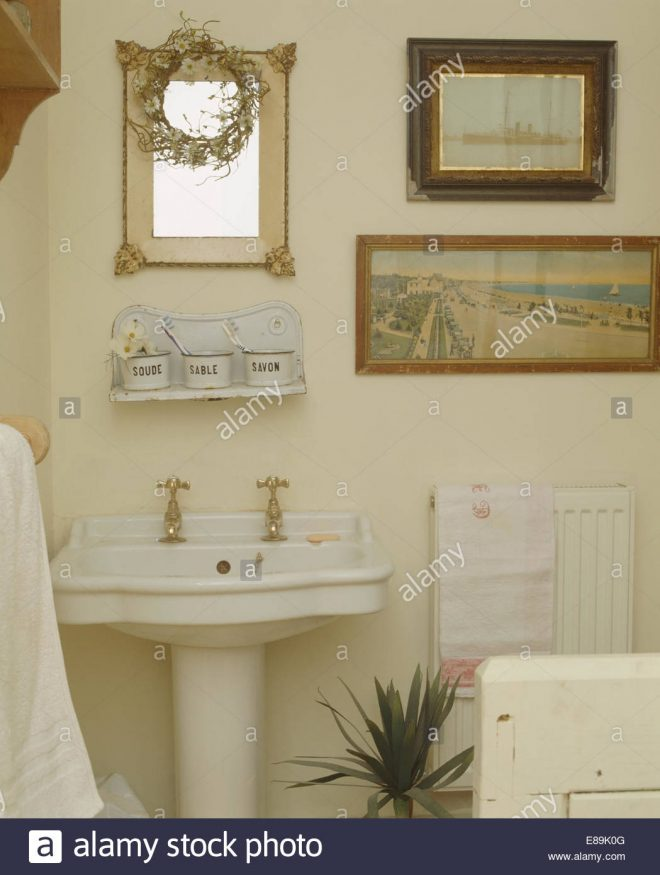 pictures and mirror above white pedestal basin in small