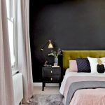pink and olive green bedroom with a black feature wall