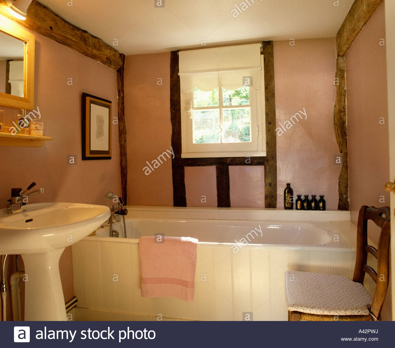 pink cottage bathroom with with beamed walls and white basin and