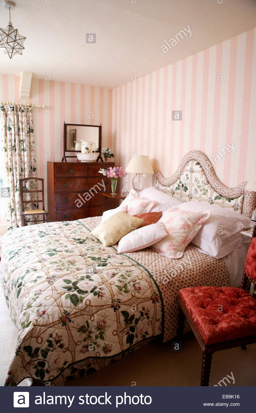 pink striped wallpaper in country bedroom with floral quilt