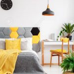 plants in colorful bedroom interior with yellow blanket on gray