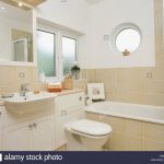 porthole window above bath in modern bathroom with neutral