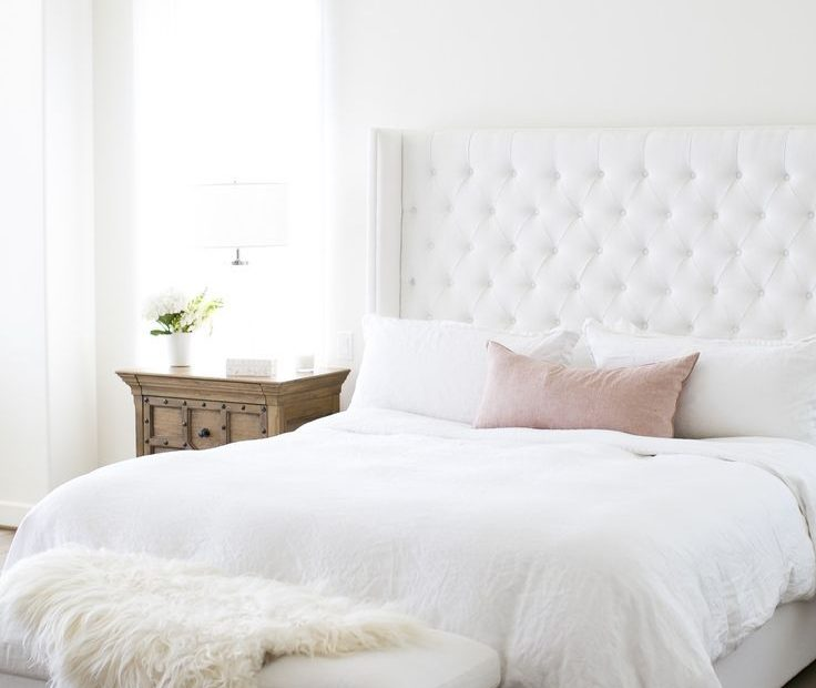 pretty and feminine bedroom with white upholstered headboard