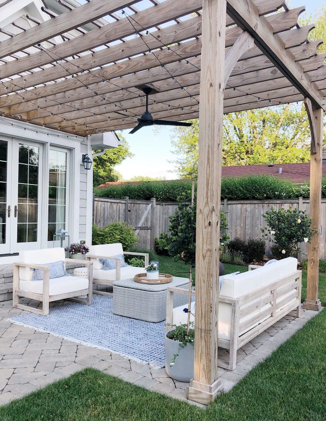 pretty outdoor space features pergola and paved patio