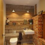 rustic bathroom with reclaimed wood and exposed brick walls