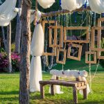 rustic wedding photo booth set up outside wooden bench with