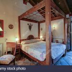 rustic wooden four poster bed in bedroom in spanish country