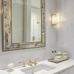 silver framed mirrors and white vanity using gold faucets for