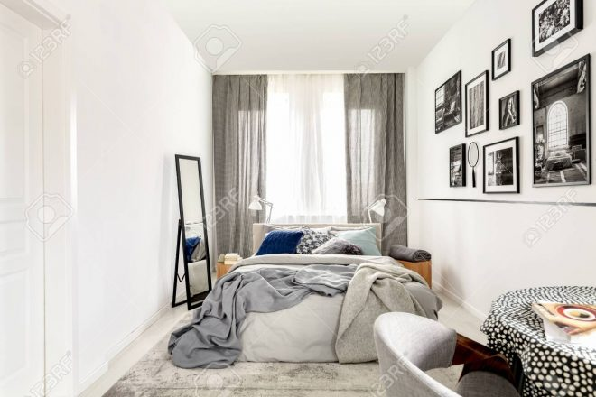 small bedroom interior with king size mirror and black and