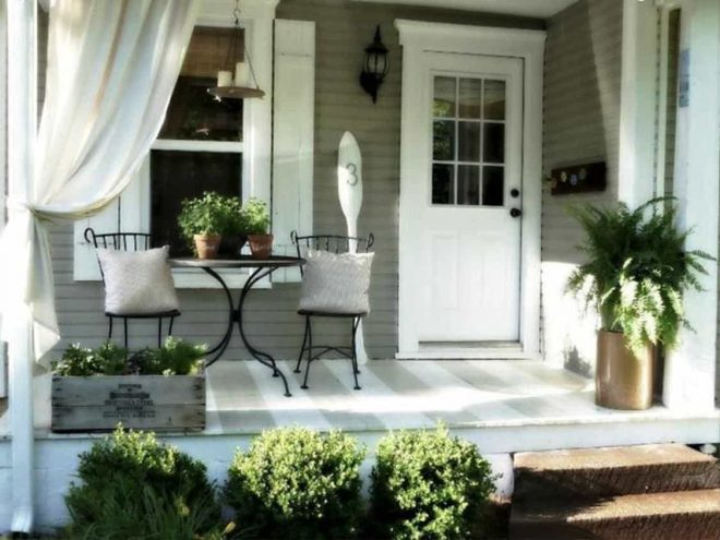 small front porch with curtains and metal furniture also plants