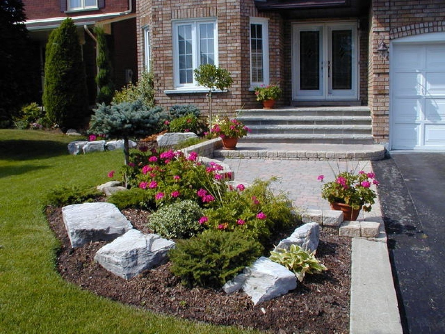 small front yard with boulders and shrubs landscaping with