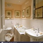 small peach bathroom with pictures and white tiling above