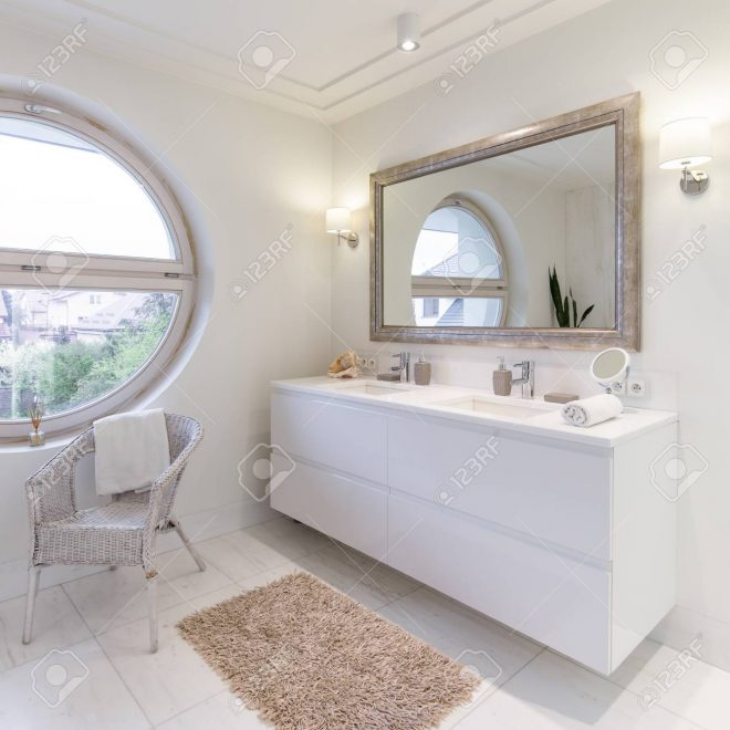 spacious bathroom with white glossy tiles big mirror and round