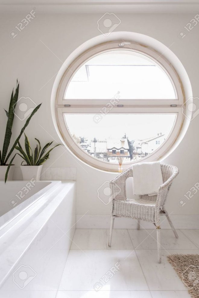 spacious bathroom with white tiling bathtub chair and round