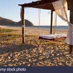 suspended outdoor bed on beach at el faro beach club and spa near