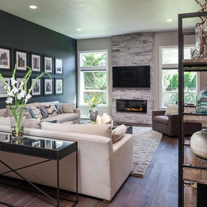 the dark accent wall fireplace and custom wood floors add warmth to