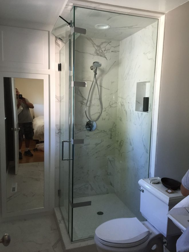this frameless floor to ceiling glass shower enclosure has a