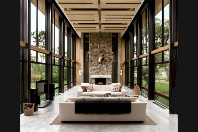 two story living room flanked floor to ceiling windows in