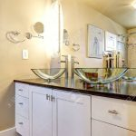 white bathroom vanity cabinet with glass vessel sinks and mirror