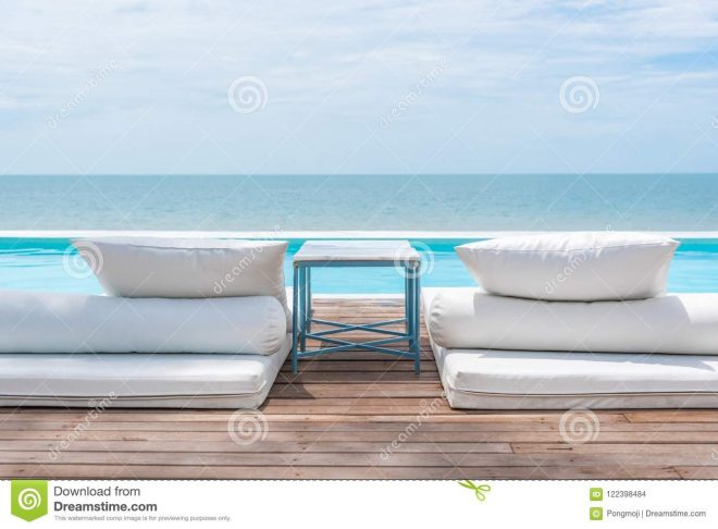 white bed at pool seaside the sea with horizon sky stock