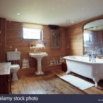 wood panelled walls and floor in country bathroom with large
