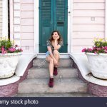 young hipster millennial woman sitting smiling happy on stairs steps