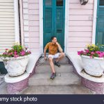 young local man sitting smiling happy on stairs steps front porch in