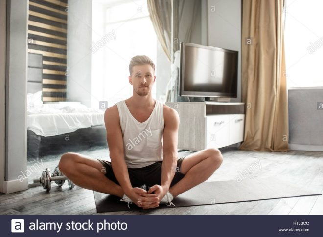 young well built man go in for sports in apartment calm and