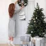 young woman hanging a christmas wreath on the door scandinavian
