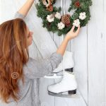 young woman hanging a christmas wreath on the door stock